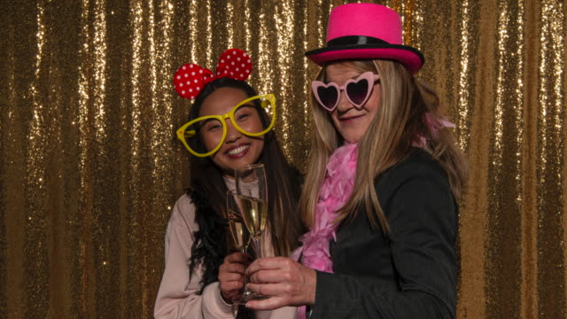 Two women wearing party glasses and hats and drinking wine while posing in the photo booth