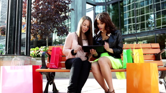 Two women with digital tablet and shopping bags video