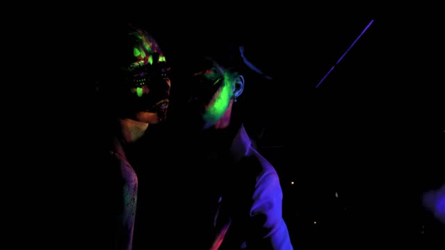 Two women with glowing fluorescent bodyart looking at camera video
