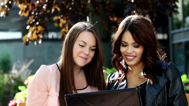 Two women with laptop and shopping bags video