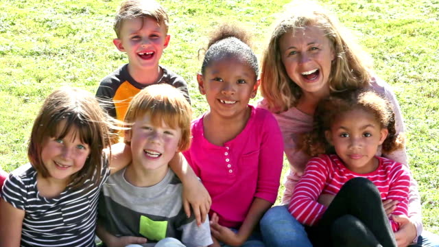 Two women with large group of children sitting on grass video