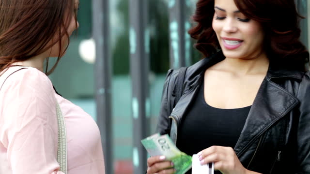 Two women with shopping bags and money video