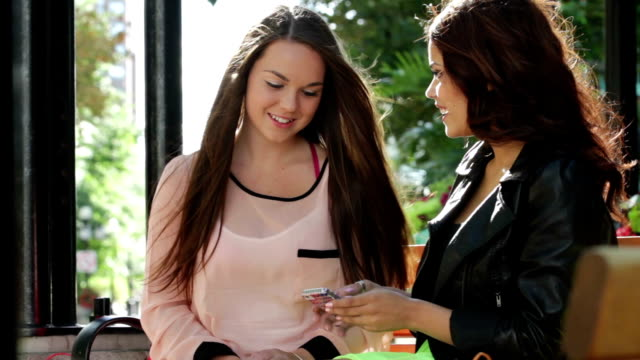Two women with smartphone and shopping bags video