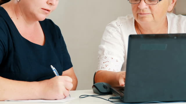 two women working on laptop video