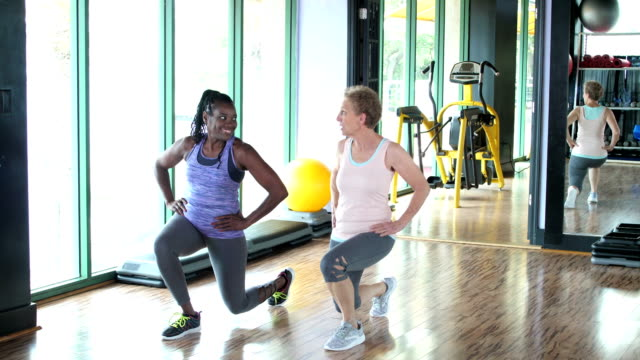 vídeos de stock e filmes b-roll de two women working out together at the gym, lunges - 55 59 anos