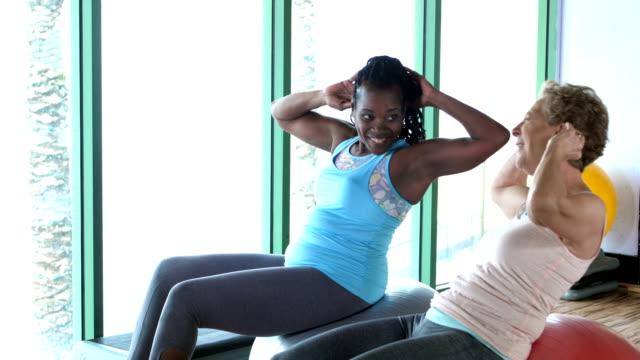 två kvinnor träna tillsammans, gör sit-ups på gym - gym skratt bildbanksvideor och videomaterial från bakom kulisserna