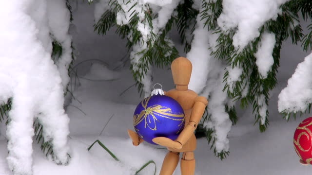 Two wooden artist models holding Christmas baubles Two wooden artist models holding Christmas baubles under snow covered fir tree marionette stock videos & royalty-free footage