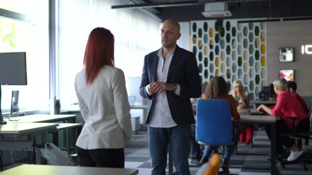 Two work colleagues talking in modern office video