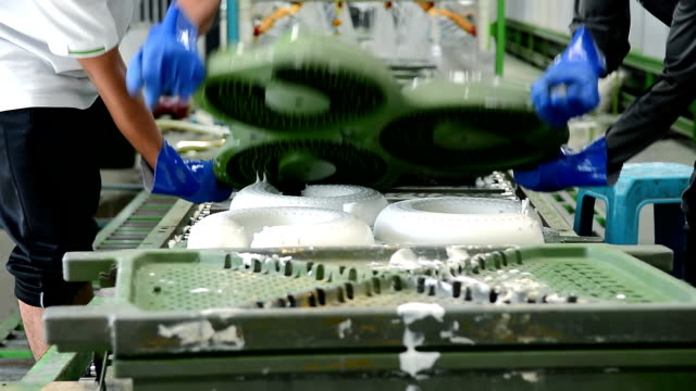 Two worker lift up metal mold of latex pillow on conveyor belt in latex pillow factory