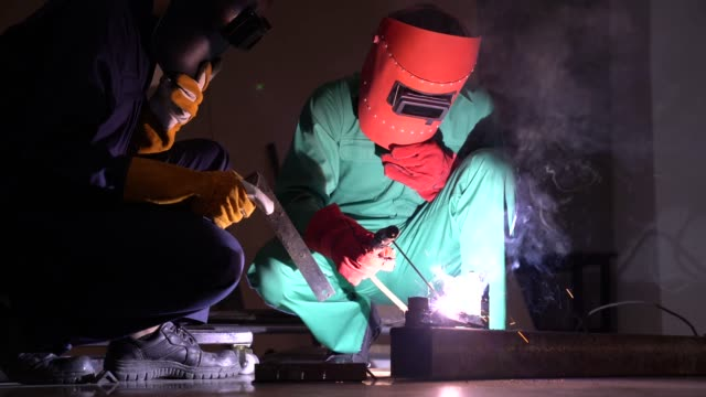 Two workers are welding steel in industrial plants, They wear safety equipment.