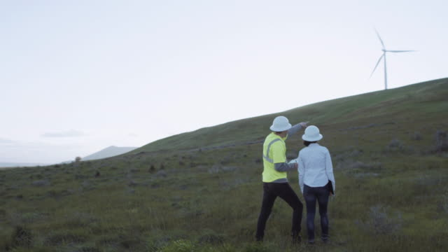 two workers in the energy out on windmill site - energia sostenibile video stock e b–roll