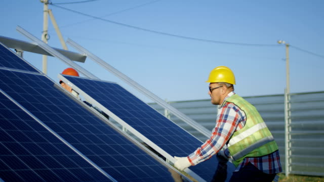 Two workers install a solar panel