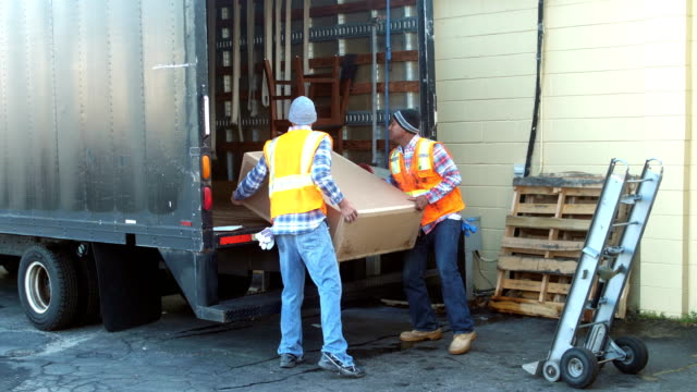 Two workers loading big box onto delivery truck