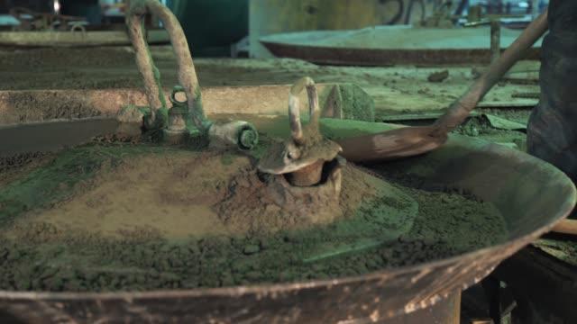 2 人の労働者に広がるセメント シャベルで金属製のボウルを機械の振動 - セメント点の映像素材/bロール
