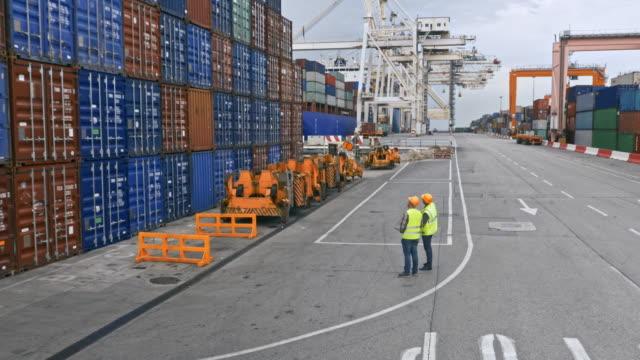 vídeos de stock, filmes e b-roll de aéreo dois trabalhadores que estão por uma grande pilha de recipientes de transporte na porta - porto distrito