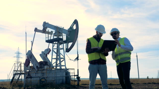 two workers standing on an oilfield near oil pumps. - due oggetti video stock e b–roll