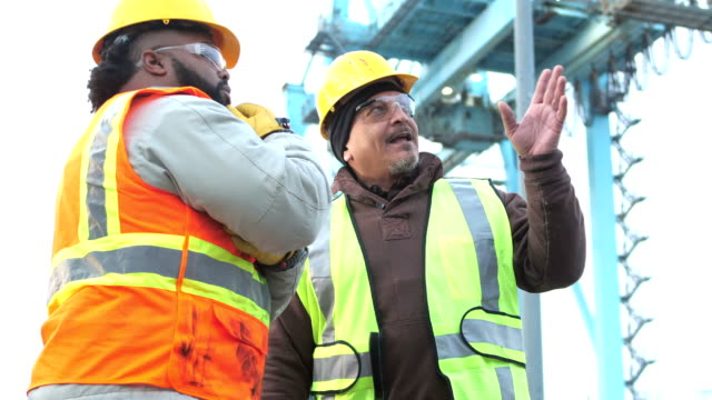 Two workers talking, working at shipping port Two multi-ethnic workers working at a seaport, wearing reflective vests, hardhats, and safety glasses. They are standing face to face. A mature Hispanic man in his 40s is talking, explaining something to the young African-American man. In the background is a gantry crane for moving cargo containers. construction machinery stock videos & royalty-free footage