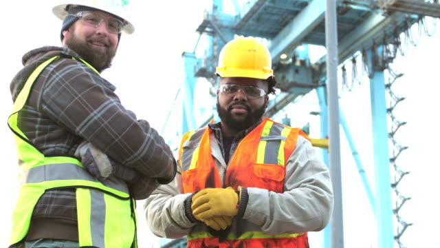 Two workers talking, working at shipping port Two multi-ethnic workers working at a seaport, wearing reflective vests, hardhats, and safety glasses. They are standing face to face. A young African-American man in his 20s is talking, explaining something to a mid adult man in his 30s. They turn and look at the camera. In the background is a gantry crane for moving cargo containers. work helmet stock videos & royalty-free footage