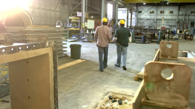 vídeos y material grabado en eventos de stock de dos trabajadores caminando por la tienda de fabricación de metal - obrero de la construcción