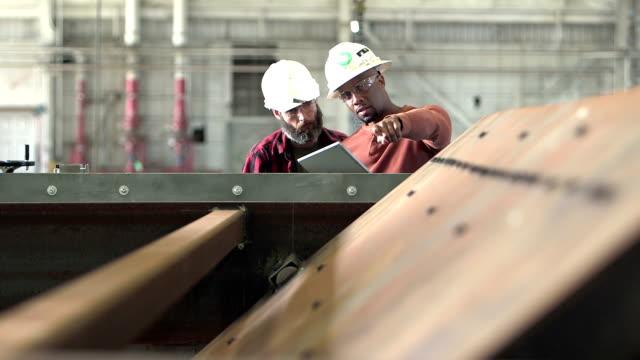 Two workers wearing hardhats, looking digital tablet