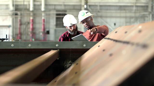 Two workers wearing hardhats, looking digital tablet video