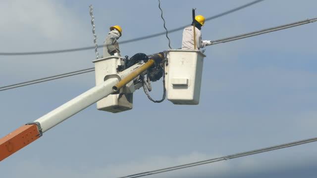 två arbetstagare bära hjälmar renovera powerline. - skylift bildbanksvideor och videomaterial från bakom kulisserna