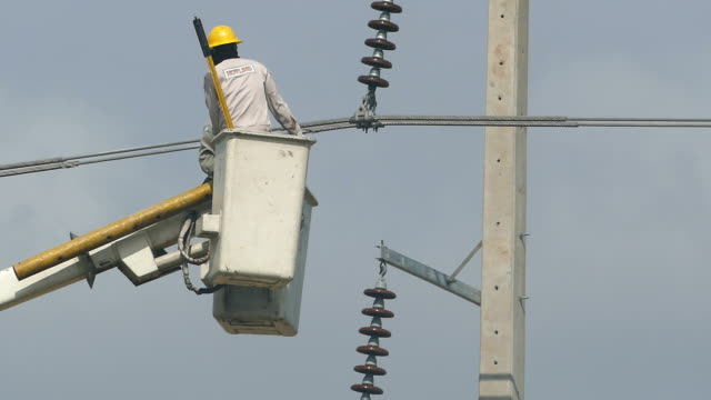 Two workers wearing helmets renovating powerline. video
