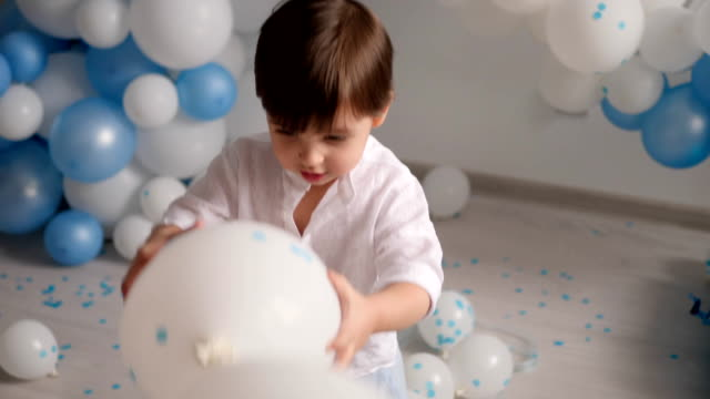 garçon de deux ans jouant avec des ballons bleus - Vidéo