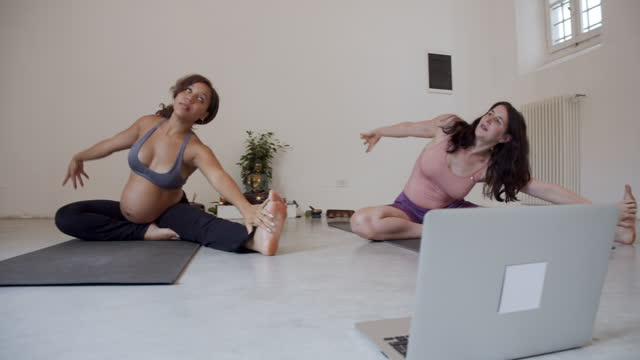 Two yogi girls are training together during an online yoga class video