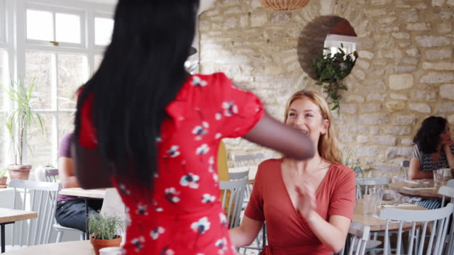 Two young adult female friends at a restaurant stand to greet a third friend who arrives to meet them at their table, close up, lockdown