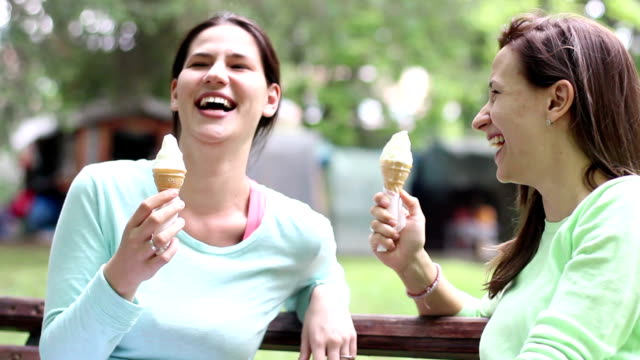 Two young and beautiful woman eating ice cream video
