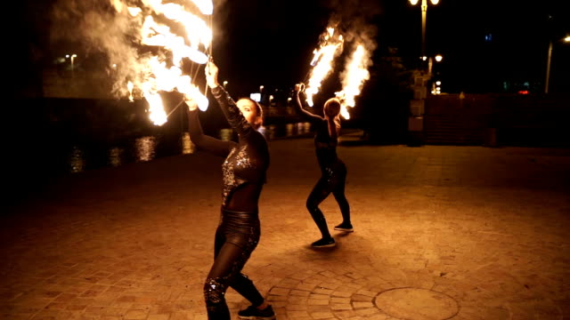Two young and beautiful young women in fire show attraction Two young and beautiful young women in fire show attraction pyrotechnic effects stock videos & royalty-free footage