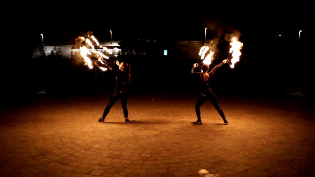 Two young and beautiful young women in fire show attraction,super slow motion Two young and beautiful young women in fire show attraction,super slow motion pyrotechnic effects stock videos & royalty-free footage