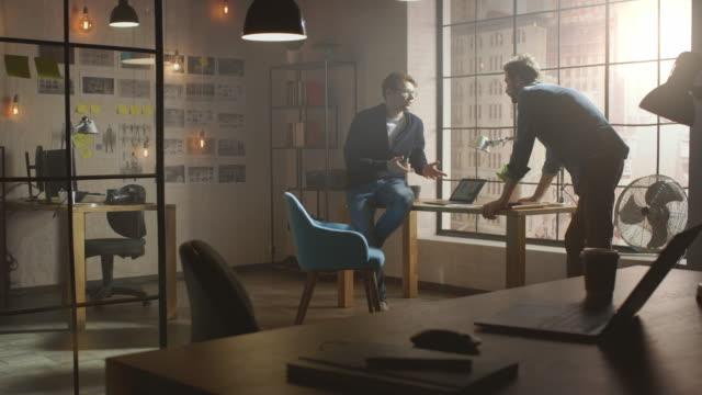 2人の若くてハンサムなデザイナーが机の上に座り、ラップトップでソーシャルメディアアプリのインターフェースについて話し合います。彼らは、近代的な都市都市の大きな窓の眺めと日当 - 編集者点の映像素材/bロール