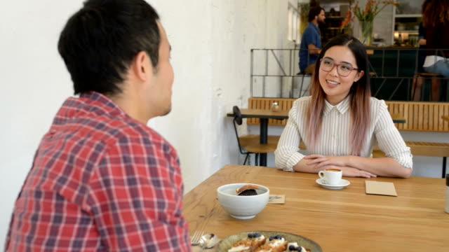 stockvideo's en b-roll-footage met twee jonge aziatische mensen zakenvergadering in cafe - 20 29 jaar