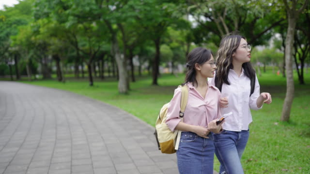 two young asian female friends  walking through park - two students together asian video stock e b–roll
