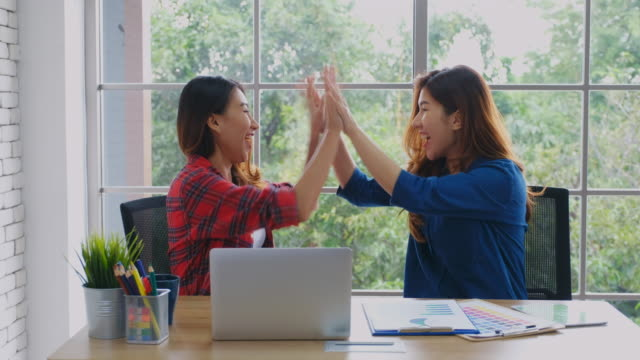 Two young asian women hand clapping when finishing work on laptop computer with successful emotion, working at home, people emotional and lifestyle