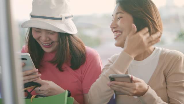 2人の若いアジアの女性が話し、電車の中でスマートフォンを使用して、スローモーション - 列車点の映像素材/bロール