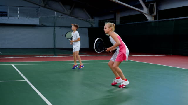 Two young athletes in recreation area playing sport game. Happy sister and brother having tennis lesson spending time at indoor court. Girl and boy serving and returning yellow balls with rackets video