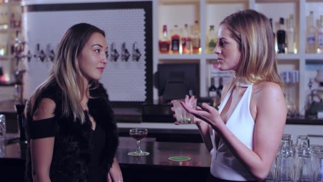 vídeos de stock, filmes e b-roll de dois jovem mulher atraente, ter uma conversa e consumindo suas bebidas alcoólicas em um bar - costumer