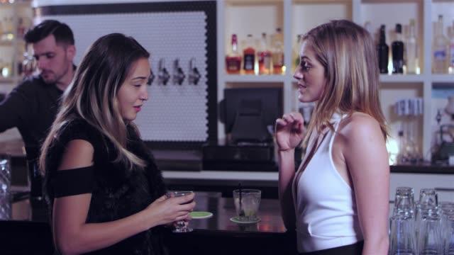 vídeos de stock, filmes e b-roll de dois jovem mulher atraente tendo uma conversa e consumindo suas bebidas alcoólicas em um bar. um deles parece preocupado - costumer