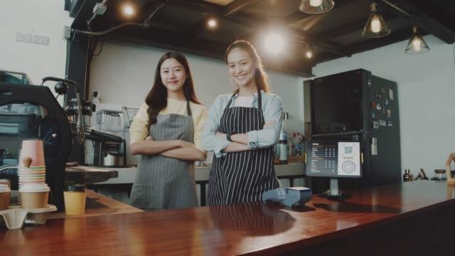 vidéos et rushes de deux jeunes beaux baristas asiatiques de femme portent le tablier parlant et restant ensemble au compteur de barre dans le café avec le visage de sourire. concept de petite entreprise de café et de café. ralenti. - relation client