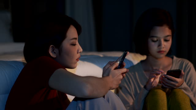 4K Two young beautiful Asian woman friends sitting in bedroom and using smartphone at night. Young woman sitting and comforting her depressed friend. Teenage problems and friendship concept.
