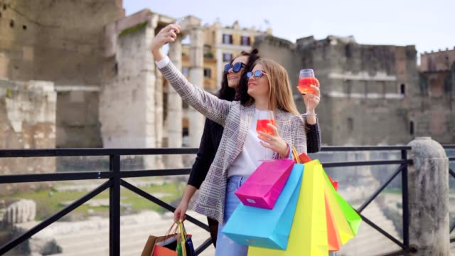 Two young beautiful girls with colorful shopping bags staying in the city centre and making selfie photos. Women hanging glasses full of fresh orange cocktail