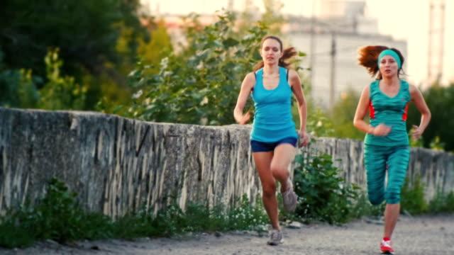 två unga vackra kvinnan körs vid stadsparken, slow motion - tävlingsdistans bildbanksvideor och videomaterial från bakom kulisserna