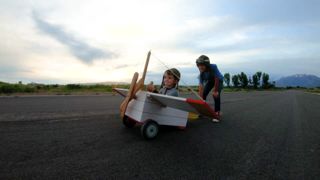two young boys flying vintage toy plane - pilota video stock e b–roll