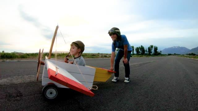 ビンテージおもちゃの飛行機を飛んでいる 2 人の男の子 - 男の子点の映像素材/bロール