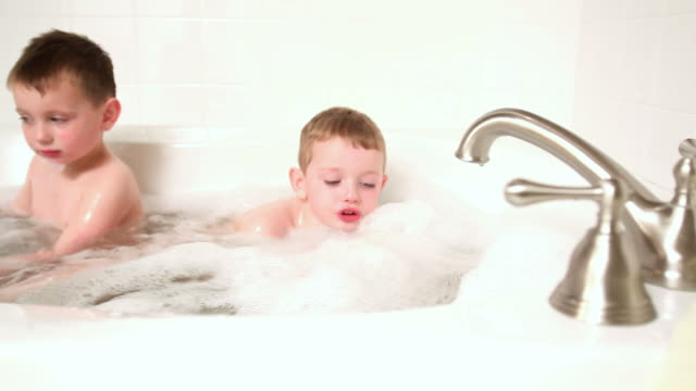 Two young boys in bubble bath, dolly movement video