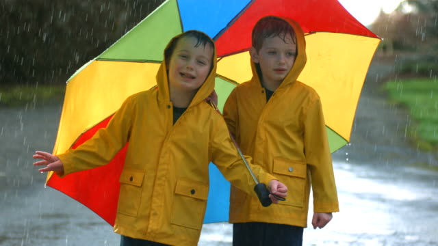 Two young boys in the rain with umbrella, slow motion video