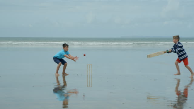 Two young boys playing beach cricket one trying to get in and the other hits the stumps! video